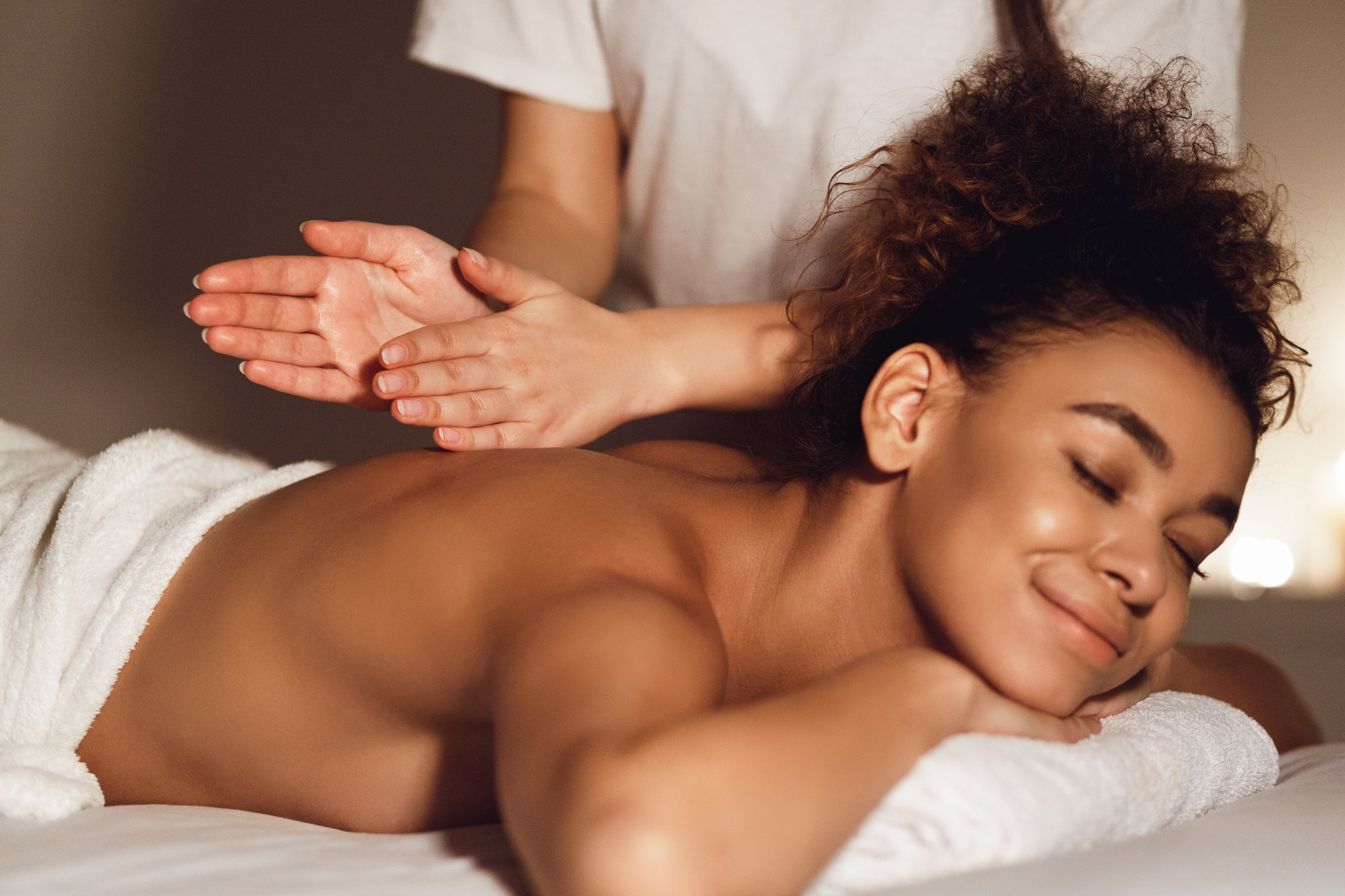 African-american woman getting spa treatment in healthy center