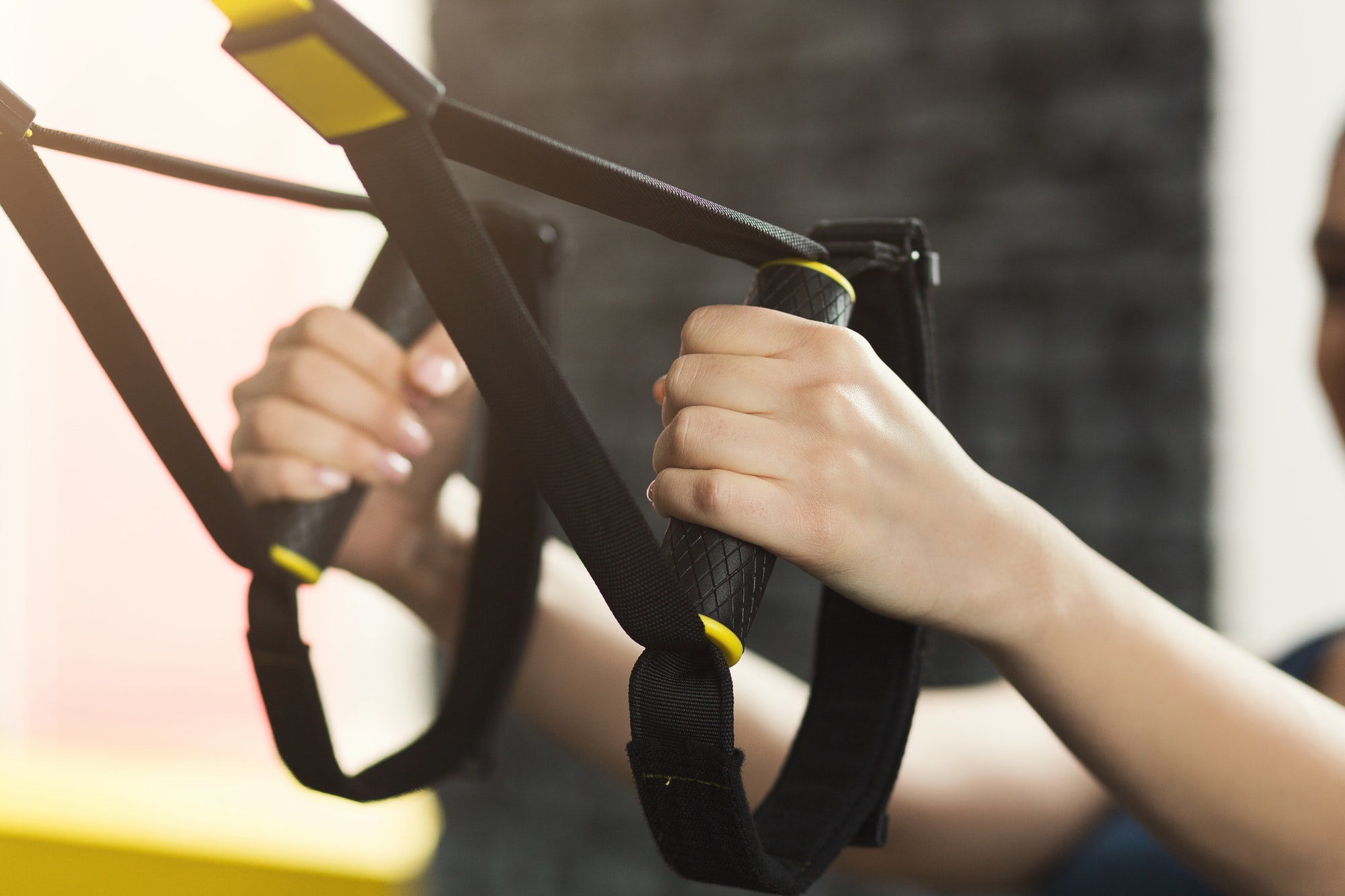 Woman performing TRX suspension training in gym