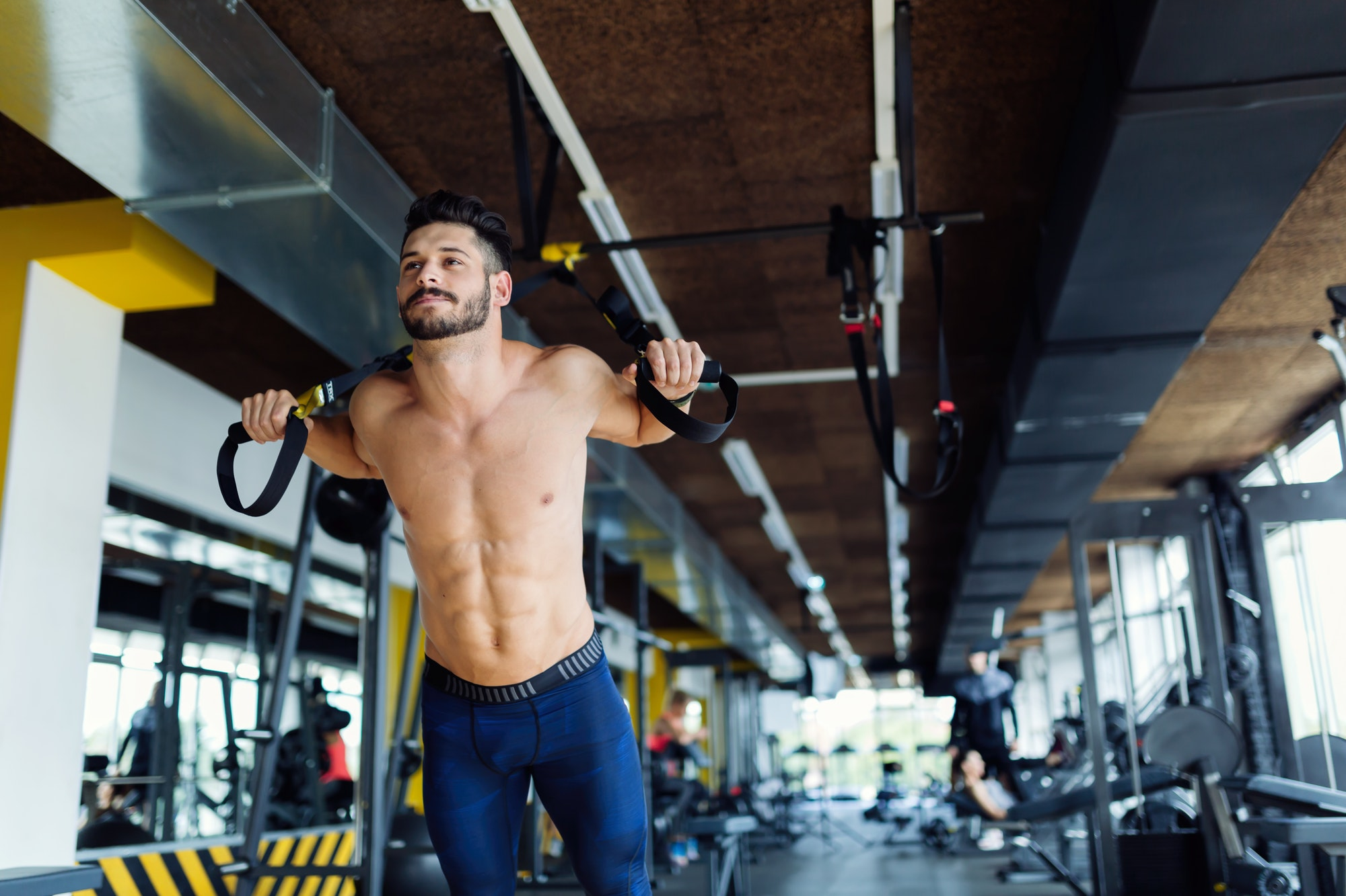 Young man doing trx exercise in gym