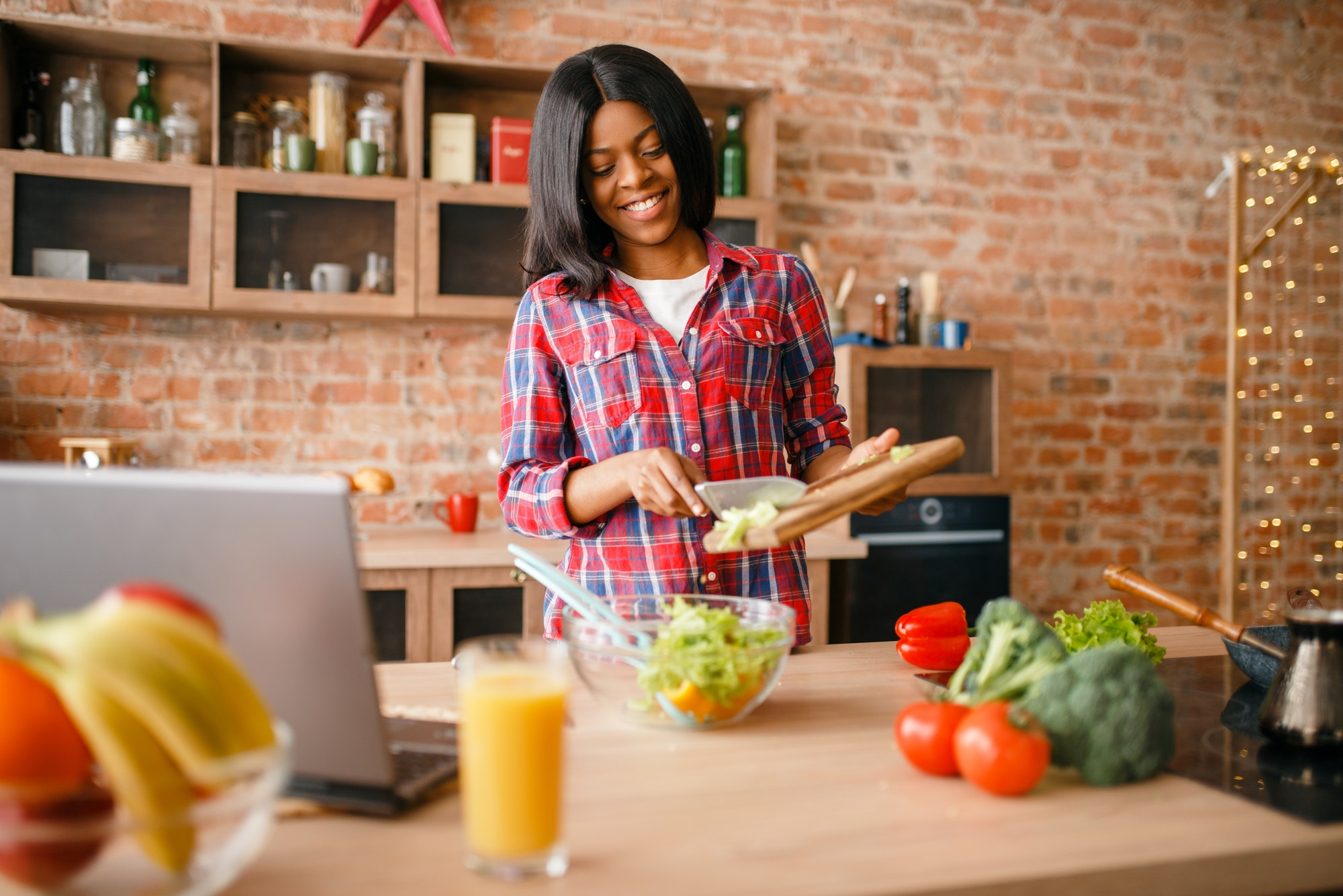 Black woman cooking salad on the kitchen