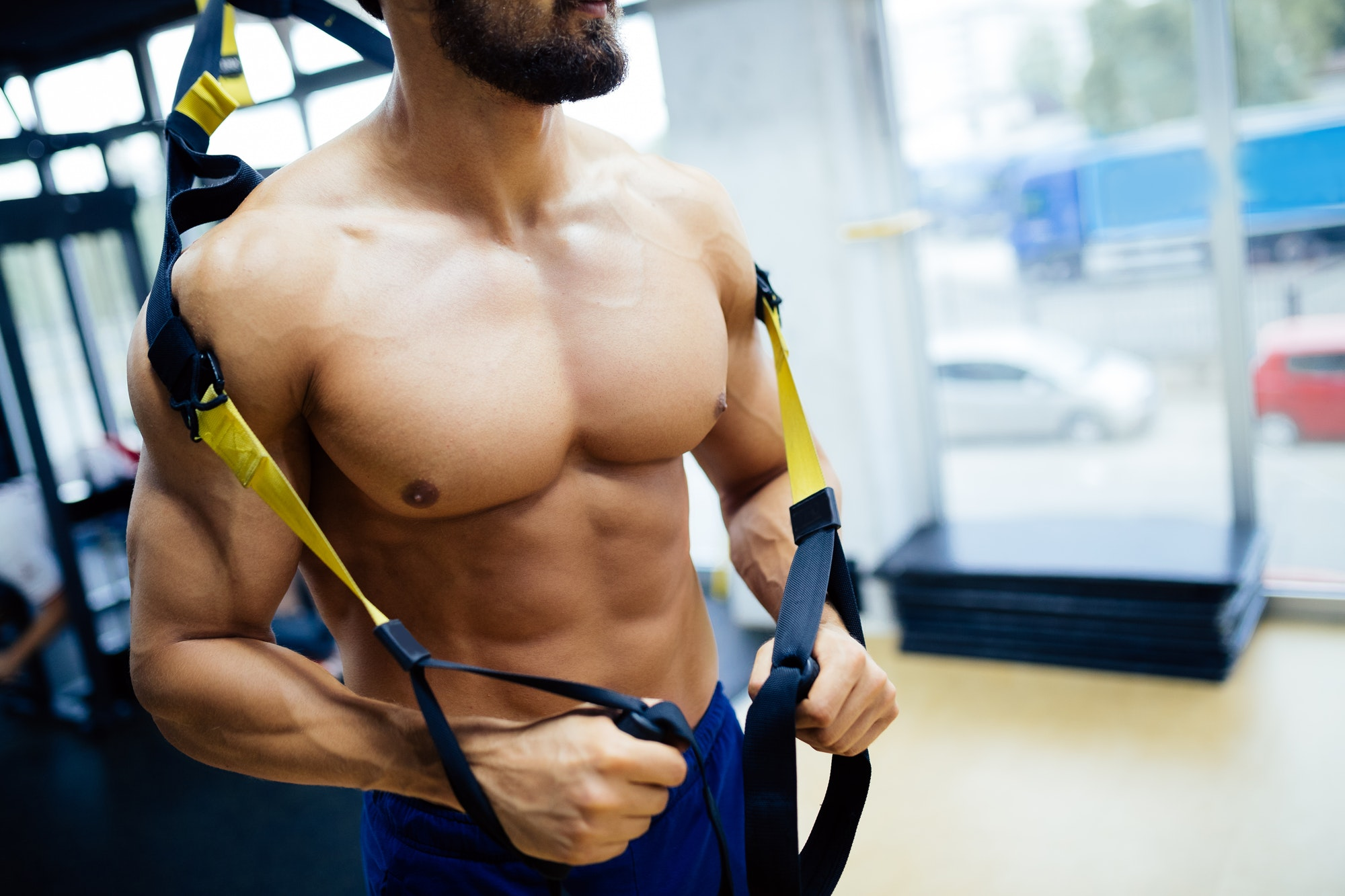 Caucasian man exercising with suspension training trx
