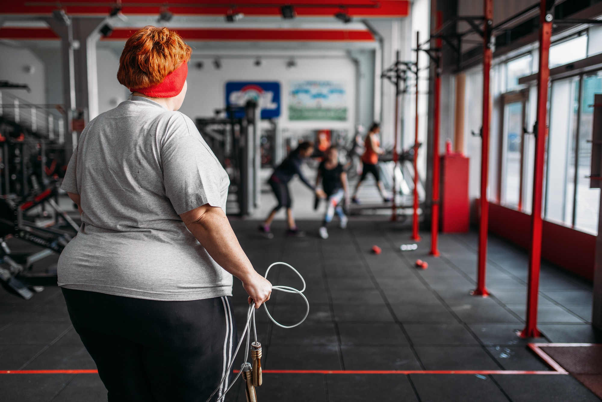 Fat sweaty woman, fit training with rope in gym