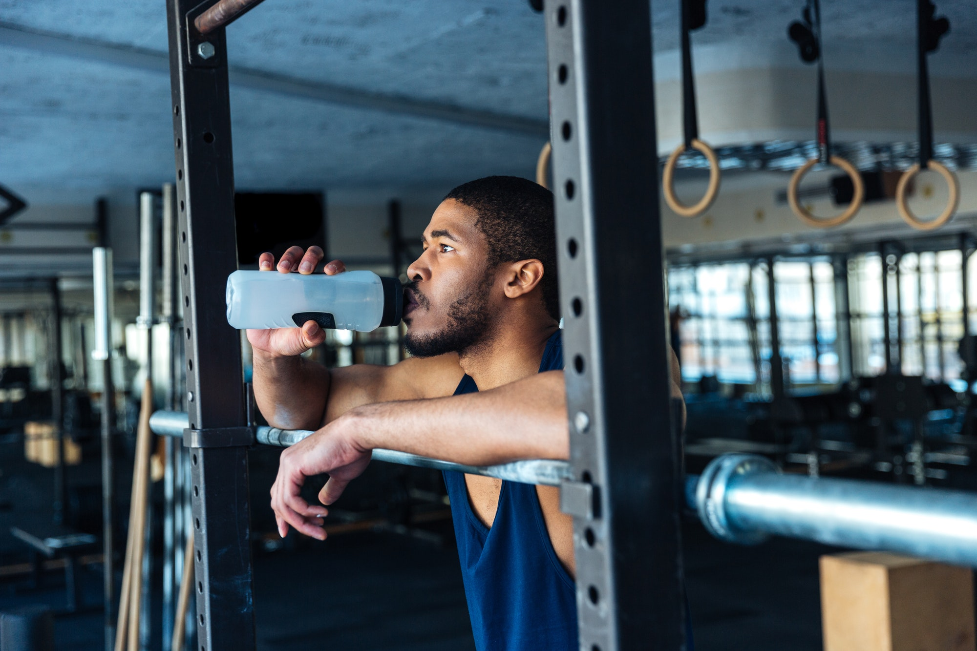 Healthy fitness man drinking water in the gym